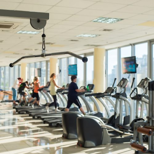 Training apparatus in gym. Picture of gym hall with training apparatus. People exercising in gym on background.